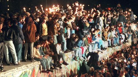"""11.11.1989, Berlin: Jubelnde Menschen sitzen mit Wunderkerzen auf der Berliner Mauer am 11.11.1989. (zu """"Themenpaket 30 Jahre Mauerfall am 9. November 1989"""")"""