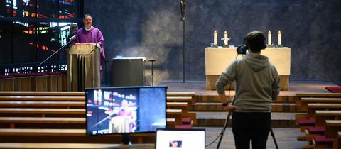 katholischer Geistlicher predigt vor leeren Kirchenbänken, Kameramann filmt