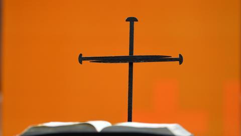 eisernes Nagelkreuz hinter einer aufgeschlagenen Bibel