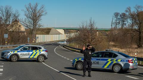Ein Polizist steht vor Polizeiwagen an dem geschlossenen tschechisch-polnischen Grenzübergang Hrádek nad Nisou/Porajów in der Region Liberec.