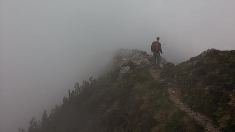 Mann läuft im Nebel auf einem schmalen Bergpfand