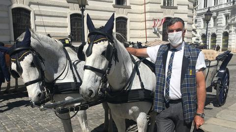 Der 53-jährige Fiaker-Fahrer Hermann Hofer wartet mit Mundschutz auf dem sonst von Touristen überlaufenen Michaelerplatz in Wien auf Kunden.
