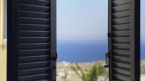 Blick durch die halb geöffneten Fensterläden eines Hotelzimmers auf das Meer,