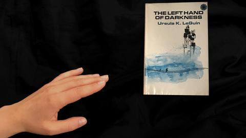 """Eine Hand, die sich nach dem Buch ausstreckt """"Ursula K. LeGuin: The Left Hand of Darkness"""""""