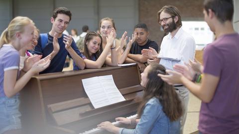 Schüler*innen stehen um Klavier herum und applaudieren