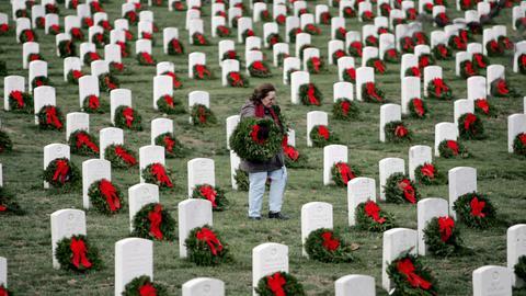 Grabsteine auf dem Militärfriedhof in Arlington bei Washington. Eine Frau legt einen Kranz nieder.