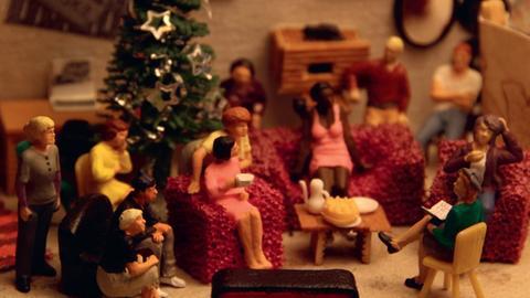 Ein weihnachtliches Wohnzimmer mit kleinen menschlichen Figuren
