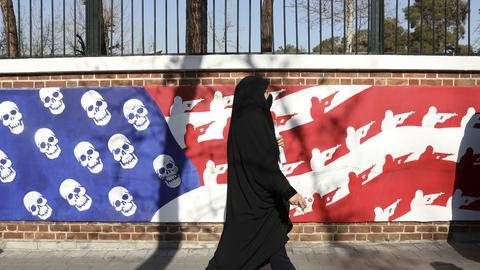 Iran, Teheran: Eine Frau kehrt von der Trauerfeier für den iranischen General Soleimani zurück, der bei einem Drohnenangriff am 03.01.2020 nahe dem Flughafen der irakischen Hauptstadt Bagdad getötet wurde. Im Hintergrund ist ein anti-amerikanisches Wandbild zu sehen, welches sich an der Wand der ehemaligen Botschaft der Vereinigten Staaten im Iran befindet.