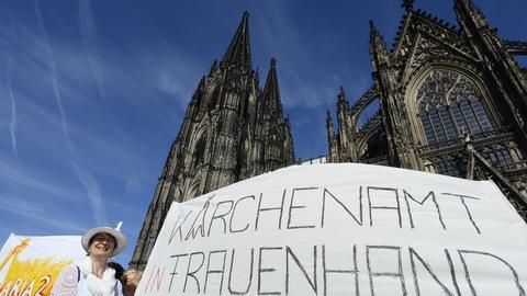 Nordrhein-Westfalen, Köln: Demonstrantinnen der Bewegung «Maria 2.0» stehen mit einem Transparent mit der Aufschrift «Kirchenamt in Frauenhand - Maria 2.0» vor dem Kölner Dom.