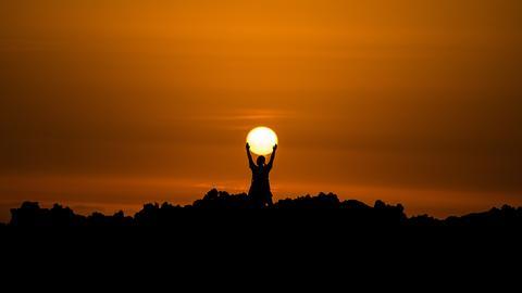 Foto mit Sonnenuntergang, sieht so aus, als ob ein Mann die Sonne in Händen hält
