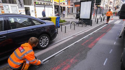 Ein Straßenarbeiter malt im Mai die Fahrbahnmarkierung für einen neu angelegten Fahrradweg am Boulevard Emile Jacqmain in Brüssel.