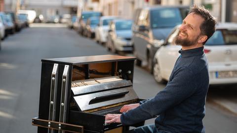 In Mainz spielt der Pianist Simon Höneß auf seinem Rollklavier mitten auf der Straße.