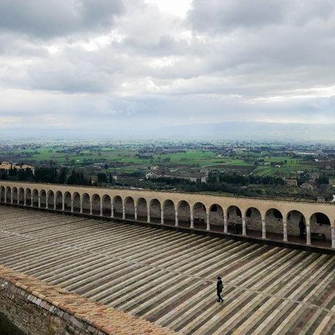 Spaziergänger auf den Arkaden der Basilika von Assisi