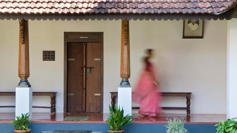 Eine Frau im Sari geht durch ein indisches Ayurveda-Hotel