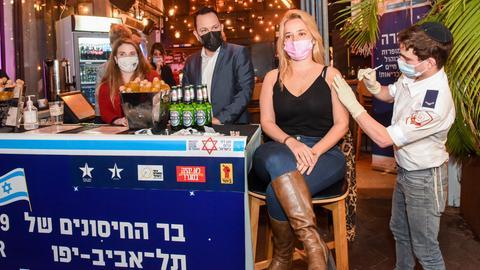 Eine junge Frau auf einem Barhocker bekommt eine Spritze in den Oberarm, daneben stehen Bierflaschen.