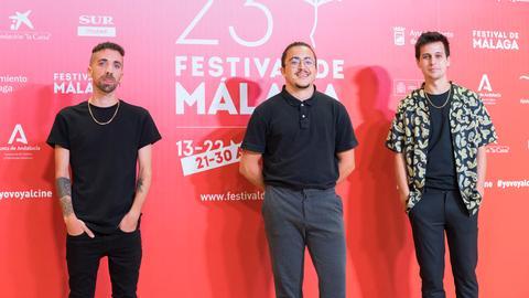 Drei junge Männer stehen vor einer Werbewand des Festivals von Malaga