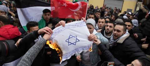 Teilnehmer einer Demonstration verbrennen am 10.12.2017 eine selbstgemalte Fahne mit einem Davidstern in Berlin im Stadtteil Neukölln.