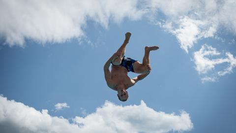 Junger Mann in Badehose fliegt durch die Luft