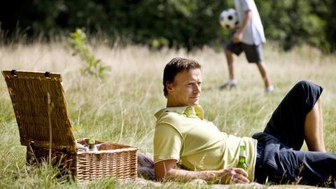 Ein Mann liegt im Park auf einer Wiese mit einem Bier in der Hand