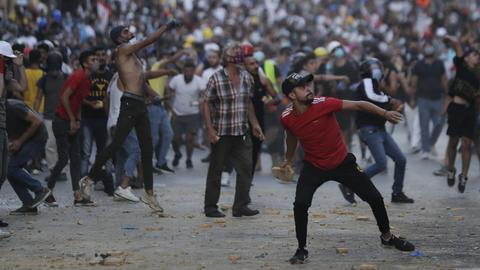 9.08.2020, Libanon, Beirut: Demonstranten werfen bei einem Protest auf einer Straße Steine. Fünf Tage nach der verheerenden Explosion im Hafen der libanesischen Hauptstadt haben Tausende Libanesen um die Opfer getrauert und gegen die politische Elite des Landes protestiert.