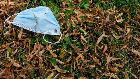 Eine Mund-Nasen-Maske liegt auf einer Wiese in einem Park.