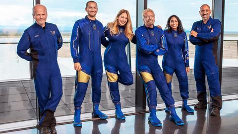 Vier Männer und zwei Frauen in blauen Phantasie-Anzügen.