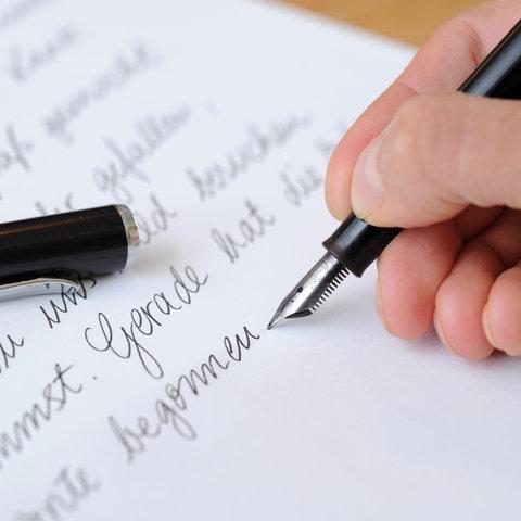 Eine Frau schreibt am 18.09.2012 in München (Bayern) einen Brief mit einem Füllfederhalter.