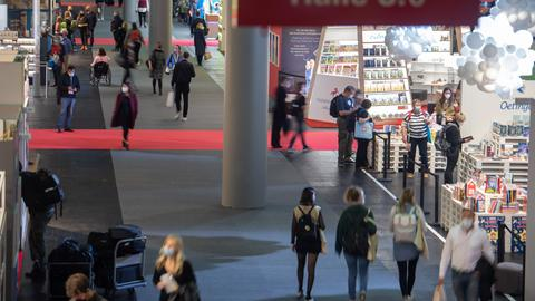 Besucher gehen am ersten Tag für Fachbesucher auf der Frankfurter Buchmesse 2021 mit viel Abstand durch einen breiten Gang. Nach der pandemiebedingten Pause 2020 darf die Frankfurter Buchmesse in diesem Jahr wieder mit Publikum stattfinden.