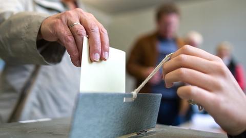 Eine Bürgerin wirft einen gelben Wahlzettel zu einem Bürgerentscheid in eine Wahlurne