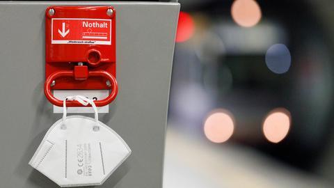 An einer Notbremse in einer Bahnhaltestelle hängt eine FFP2-Maske. Der Bundestag soll am kommenden Mittwoch über die sogenannte Bundes-Notbremse entscheiden. Die von der Bundesregierung geplanten Änderungen am Infektionsschutzgesetz sehen unter anderem eine nächtliche Ausgangssperre vor.