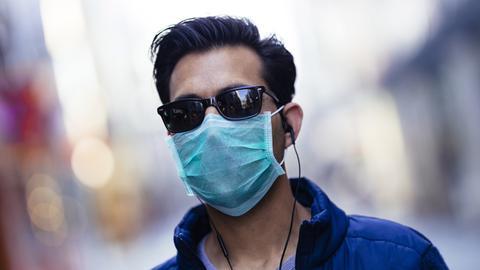 Ein Passant posiert mit einer Behelfsmaske auf der Hohe Straße. Köln,