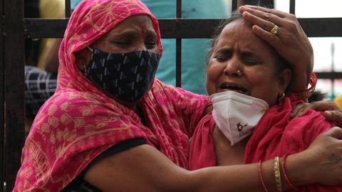 Zwei Fraune trauern über ein Corona-Opfer vor dem Lok Nayak Jai Prakash Narayan Hospital in Neu Dehli