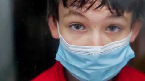 Teenage mit medizinischer Maske zu hause hinter einem Fenster