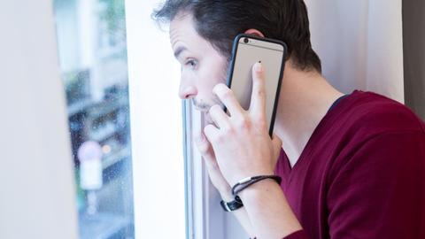 Ein Mann steht in einer Wohnung in Hamburg am Fenster und telefoniert mit seinem Smartphone (gestellte Szene).