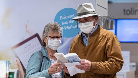 Ein Ehepaar aus Wörth schaut sich im Buchladen mit Mundschutz Bücher an. GES/ Tägliches Leben in Deutschland während der Corona-Krise.