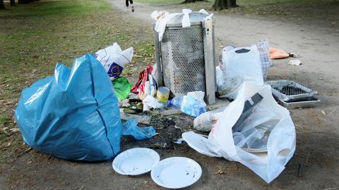 Der Müll vom Picknick des Wochenendes liegt in einem Park in Düsseldorf.