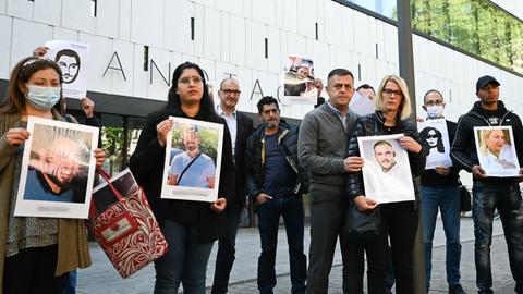 Angehörige stehen mit Fotos der Opfer des rassistisch motivierten Anschlags von Hanau vor dem Hessischen Landtag.