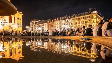 Menschen sitzen am Abend rund um den Brunnen vor der Alten Oper.