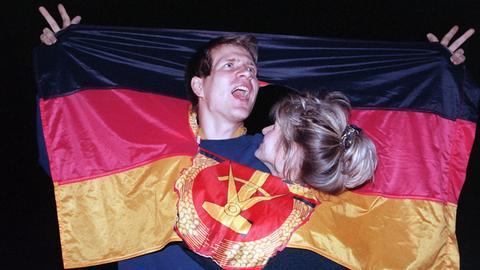 ARCHIV - 03.10.1990, Berlin: Ein jubelnden Paar hat sich am Tag der Deutschen Einheit in einer DDR-Fahne dort Platz geschaffen, wo früher das Emblem Hammer und Sichel war - und feierte frenetisch den historischen Anlaß.