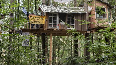 Baumhäuser und Hütten aus Holz stehen in einem der Protestcamps im Dannenröder Forst. Hunderte Aktivisten protestieren hier seit Monaten gegen die Rodung des Dannenröder Forsts und den politisch umstrittenen Weiterbau der Autobahn 49.