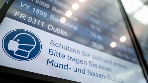 """Auf einer Anzeigetafel im Flughafen Düsseldorf steht der Hinweis """"Schützen Sie sich und andere. Bitte tragen Sie einen Mund- und Nasen-Schutz""""."""