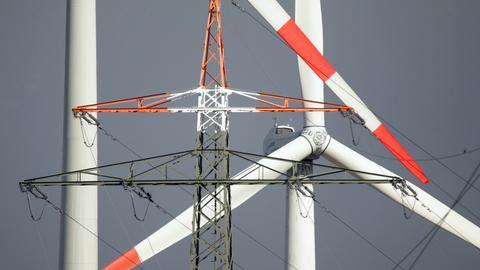 Nordrhein-Westfalen, Erkelenz: Windräder und Strommast stehen am Rande des Braunkohletagebaus Garzweiler.