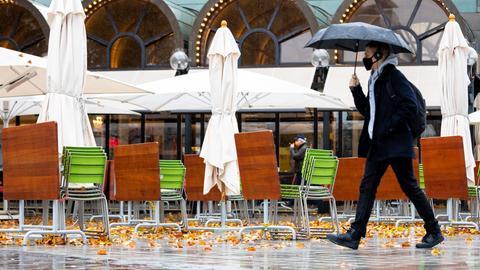 Zusammengeklappte Stühle, Tische und Sonnenschirme sind in einem Außengastronomiebereich in der Innenstadt zu sehen. Bund und Länder haben ab dem kommenden Montag einen Teil-Lockdown beschlossen.
