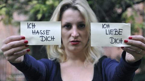 """Eine Frau hält zwei Zettel mit den Aufschriften """"Ich hasse dich"""" und """"Ich liebe dich"""" vor sich."""