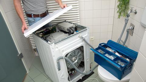 Ein Mann öffnet in einem Badezimmer eine Waschmaschine, um sie zu reparieren.