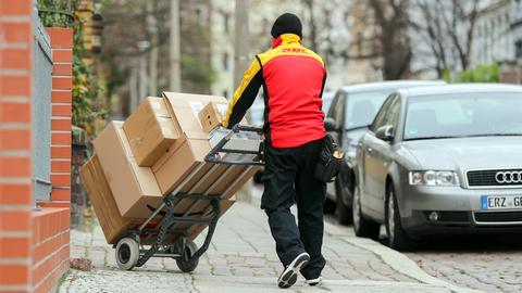Ein DHL Paketzusteller geht mit einer Sackkarre voll beladen mit Paketen zu einem Haus im Paulusviertel. DHL rechnet für die Tage vor Weihnachten mit einem neuen Rekord von Paketzahlen. Erwartet werden 11 Millionen Pakete am Tag, das Jahresmittel liegt bei 5 Millionen pro Tag.