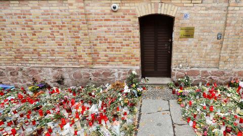Nur noch ein schmaler Weg führt zwischen den Blumen und Kerzen zur Tür der Synagoge Halle.