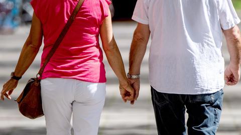 Zwei Senioren halten am 17.04.2020 auf der Strasse in Berlin händchen.