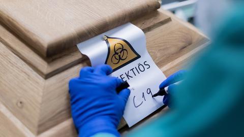 Christoph Kuckelkorn, Bestattungsunternehmer und Präsident des Festkomitees Kölner Karneval, schreibt «C19» auf ein Schild mit dem Hinweis «Infektiös» auf einen Sarg mit einem Verstorbenen, der an oder mit dem Coronavirus gestorben ist.