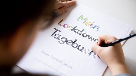 Ein Grundschüler malt an einem Tisch im Wohnzimmer die Buchstaben eines Lockdown Tagebuchs aus.